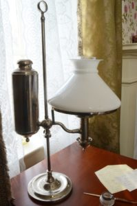 a lamp and preserved examples of Dickinson's writing on her desk