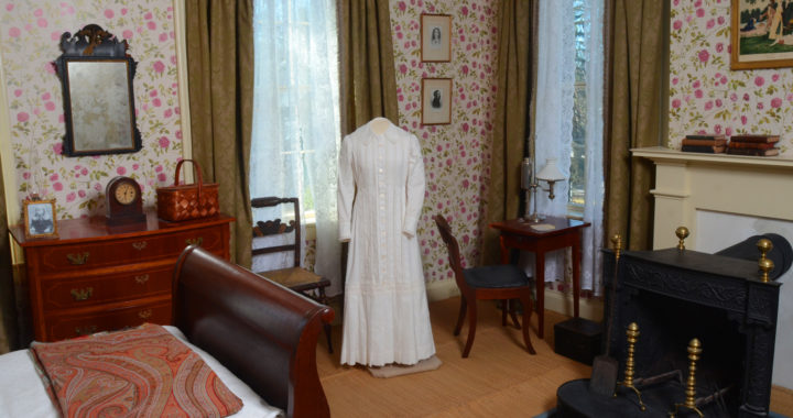 Emily's bedroom with her dress and bed and writing table