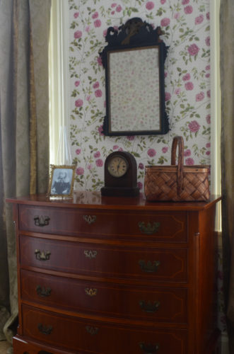 The bureau in Emily Dickinson's bedroom with a clock, a basket, and a photograph of her nephew Gib on it.