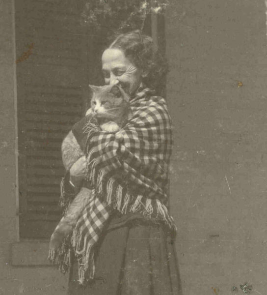 black and white photograph of Lavinia Dickinson wearing a checkered shawl and holding a cat