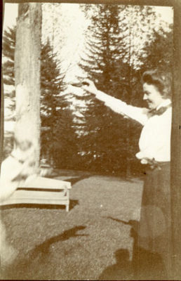 Black and white photograph of a young Martha playing with a pet dog