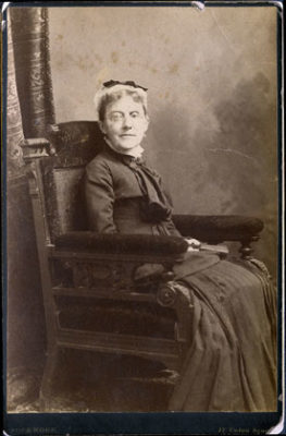 black and white photograph of a seated woman wearing spectacles