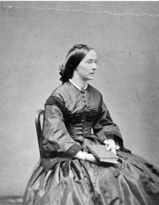 black and white photograph of a seated woman in 1860s clothing