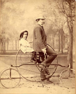 black and white photograph of Higginson with his young daughter upon a two-person bicycle