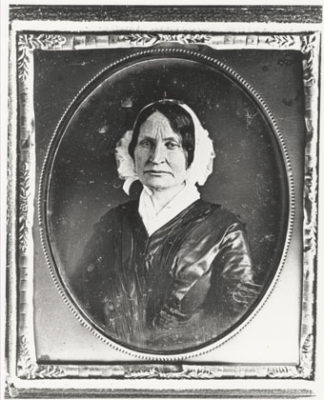 black and white photograph of a woman wearing a white bonnet