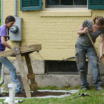 Two volunteers dig in the garden at the Emily Dickinson Museum