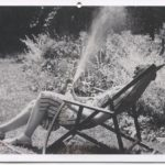Black and white postcard depicting a photograph of Eudora Welty sitting outside by a sprinkler and a garden