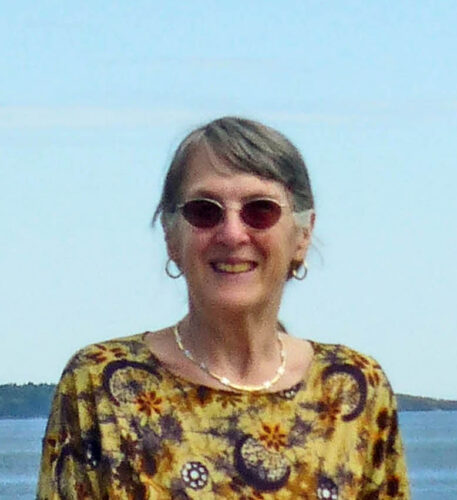 A photo of author Kathryn Holzman in front of an ocean vista