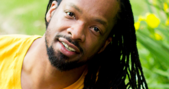 picture of Jericho Brown: a black man wearing a yellow t-shirt smiles in front of some daffodils