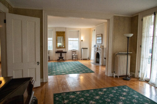 The parlor at the Homestead. Wide-shot featuring a doorway, two chairs, a desk, a gold framed mirror, and the fireplace