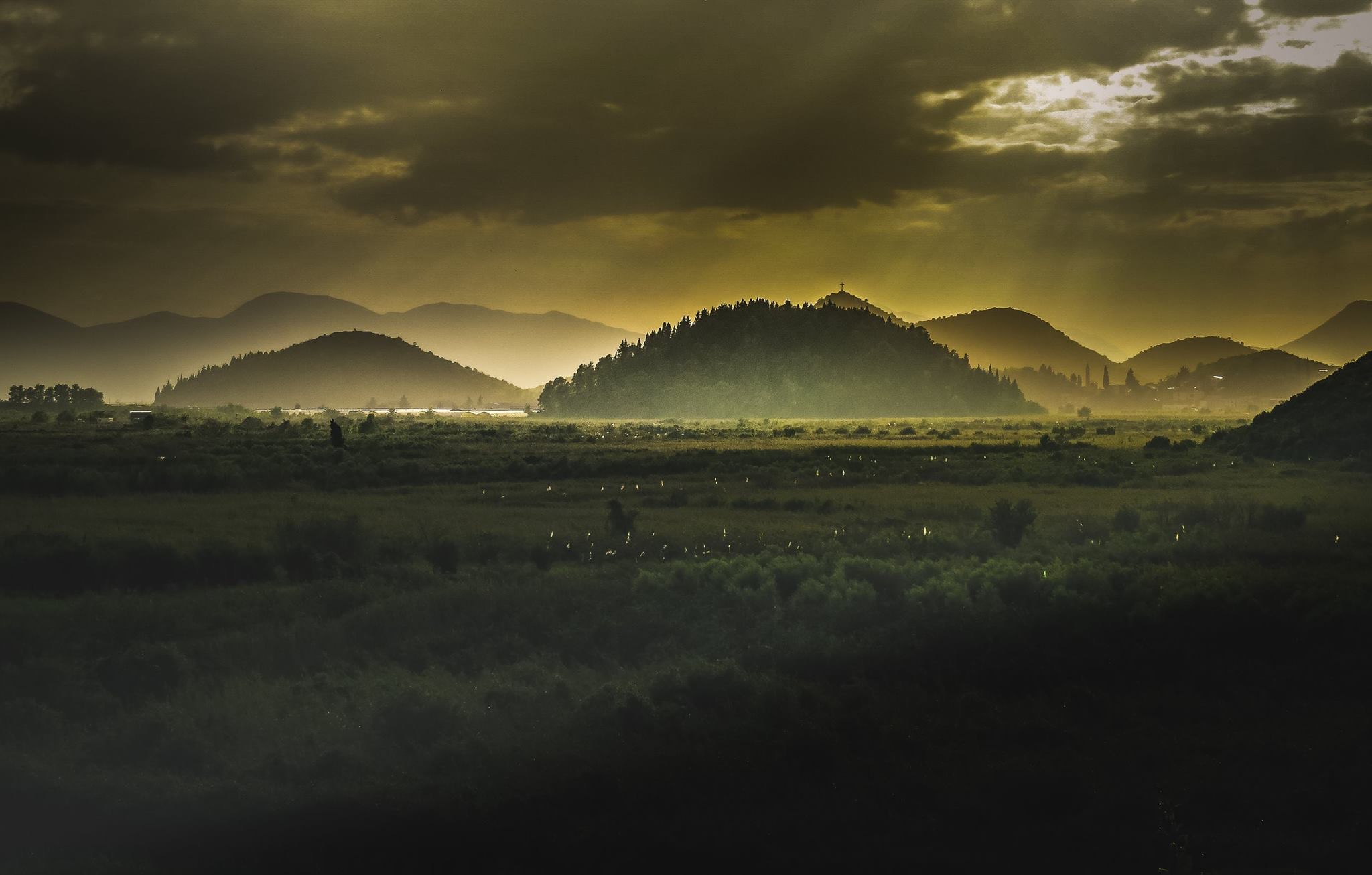 A photo taken from the perspective of a cemetery in Bosnian, featuring rolling, misty hills on a thickly cloudy day; In the foreground is a seemingly endless expanse of field. The whole photo is in tones of deep yellows, greens and blacks.