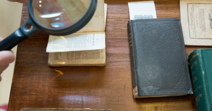 Closeup of a hand holding a magnifying glass over antique books.