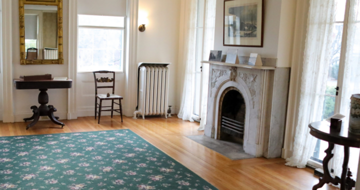 The homestead parlor with 4 windows, a fireplace, two chairs, a rug and a side table.