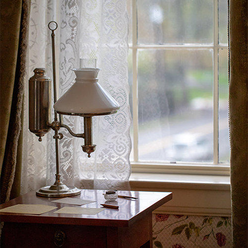 image of a small desk with lamp in front of a paned window