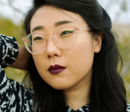 Photo of Franny Choi, looking away from the camera with one arm behind her head. She has long black hair that is pulled back behind her ears, dark red lipstick and clear glasses.