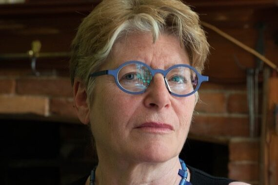 a woman with short blonde hair, blue glasses, and blue necklace stands in front a fireplace