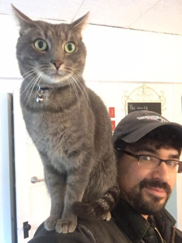 Michael Medeiros appears with a gray cat on his shoulder.
