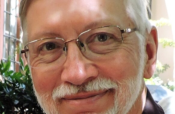 headshot of a man with white hair, mustache, beard and glasses