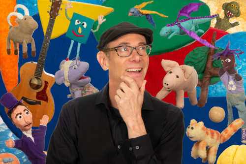Tom Knight surrounded by puppets